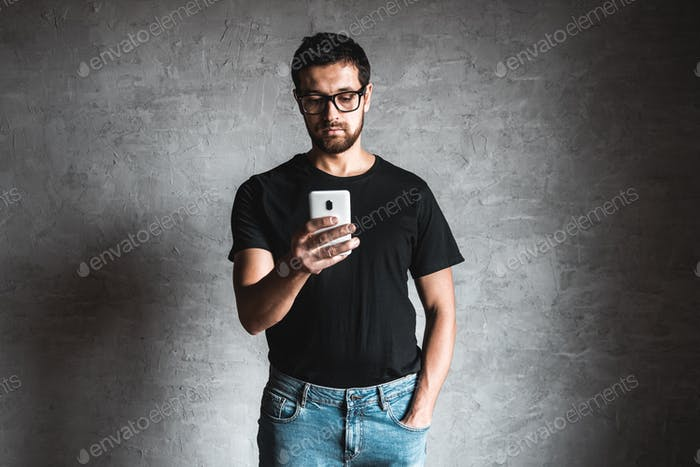 Man using his smartphone in front of a grey wall
