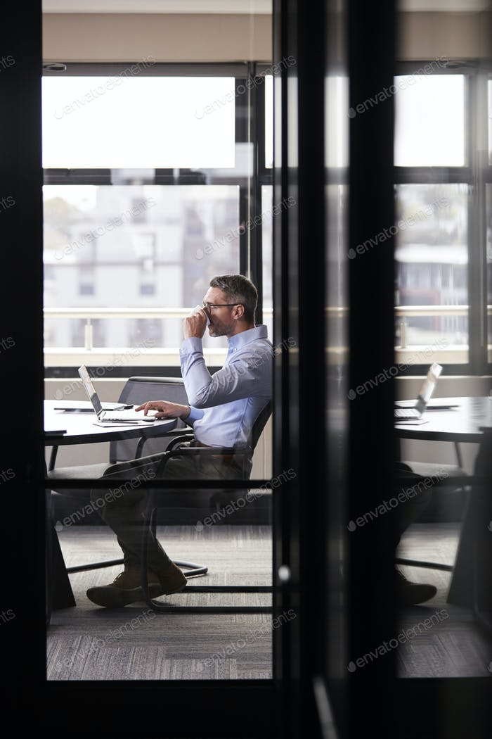 Middle aged white businessman drinking coffee and working alone in a meeting room, vertical