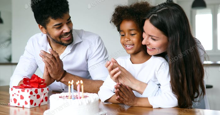 Young happy family celebrating the birthday in a living room
