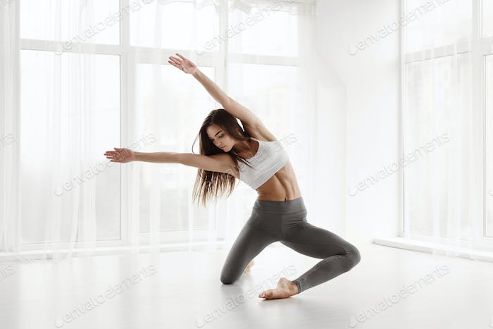 Contemporary Female Ballet Performer Training In Spacious Studio
