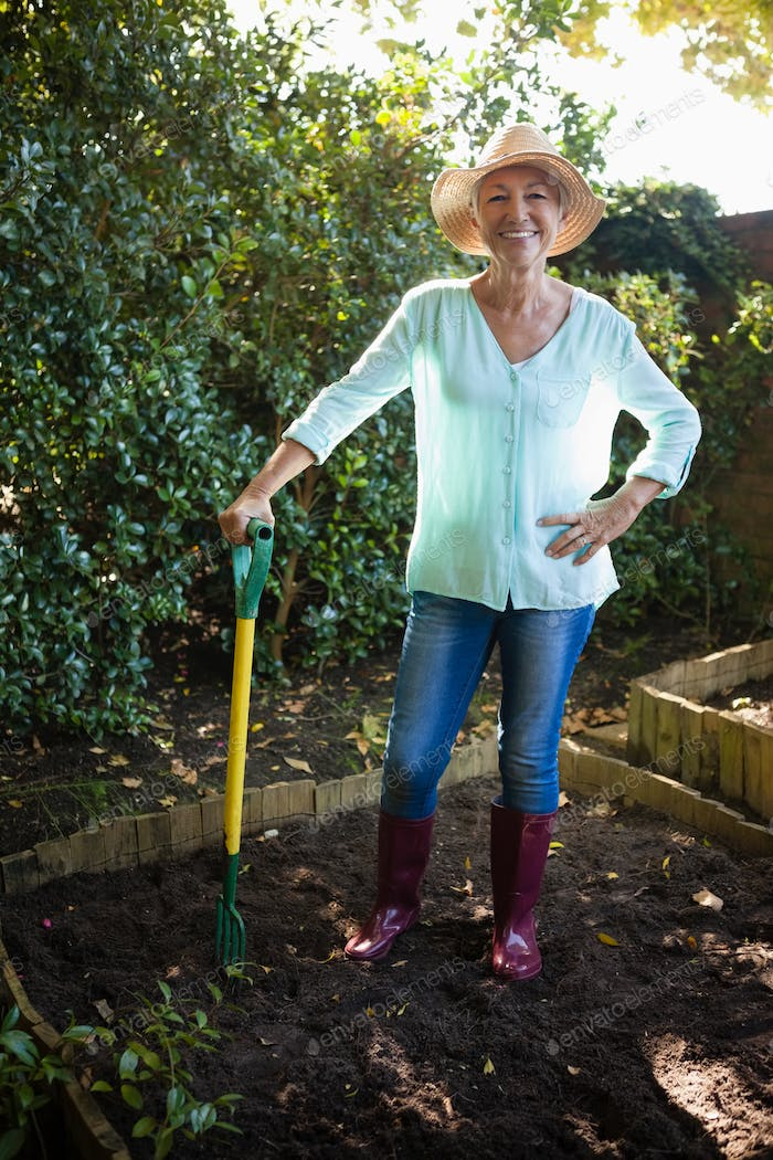 Smiling senior woman wearing hat standing with garden fork on dirt