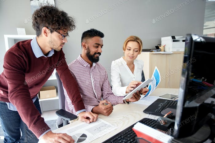 business team with tablet pc and papers in office