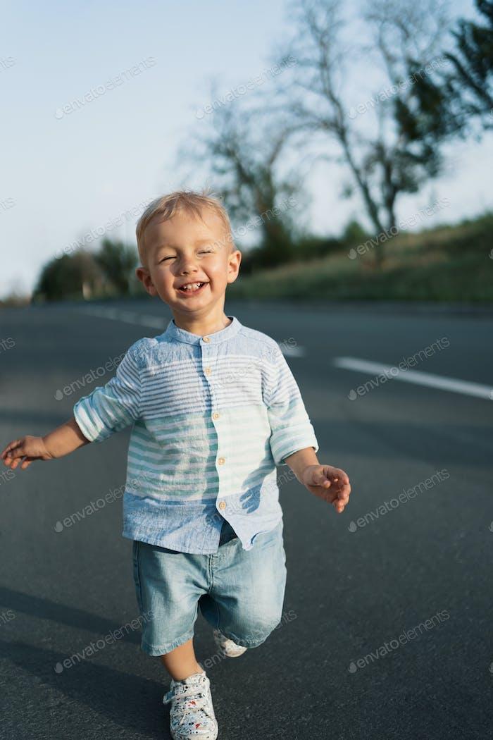 Little boy walking on the road