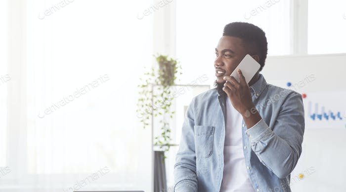 Handsome black worker talking by mobile phone in office