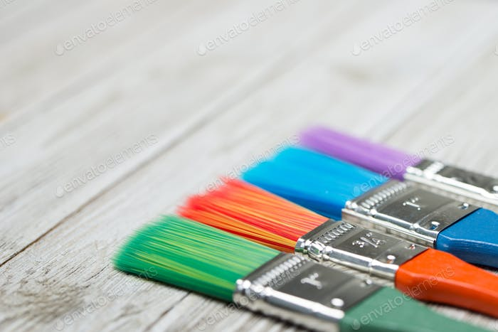 Multicolor paint brushes on grey wooden background