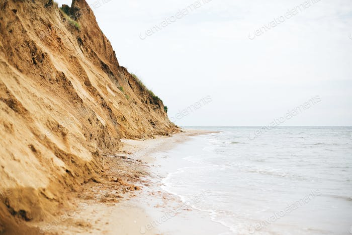 Beautiful sandy cliff with grass and sea waves on beach with on tropical island