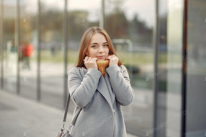 Mädchen stehend an dem großen Gebäude in einem grauen Mantel
