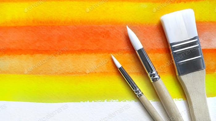 Bright watercolor background and paintbrushes