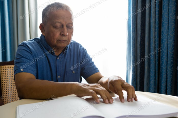 Senior man reading braille book in retirement home