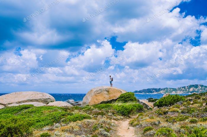 Tourist on top of sandstone rock near Costa Serena, Sardinia, Italy