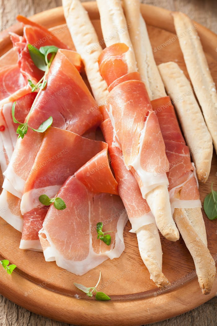 sliced prosciutto ham and grissini bread sticks