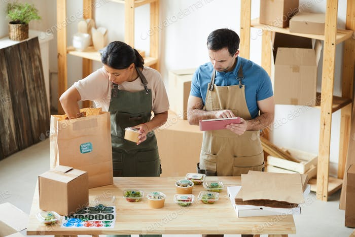 Workers Packaging Orders at Food Delivery Service
