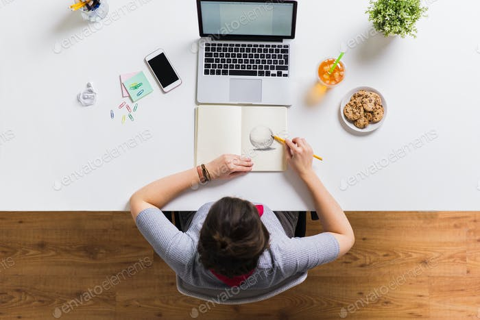 woman with laptop drawing in notebook at office