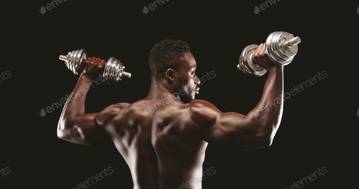 Strong black guy pumping barbells over black studio background