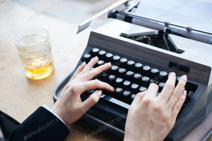 Woman's hands writing on old typewriter