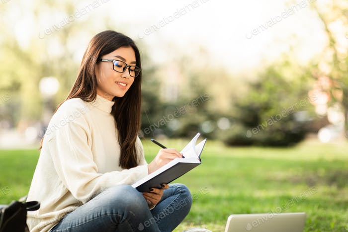 Girl writing in diary, sitting in modern parkland