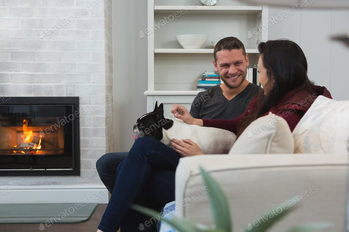 Couple relaxing with their pet dog in living room at home