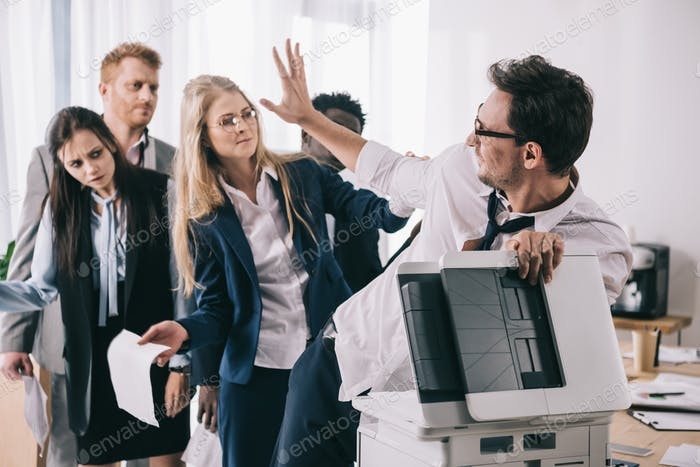 group of businesspeople fighting for copier at office