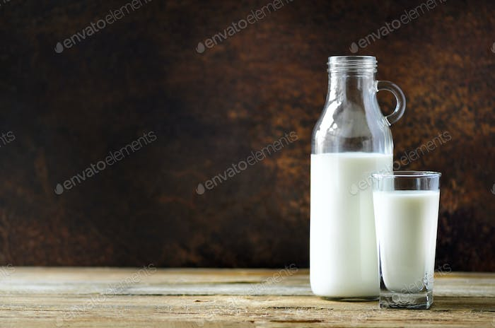 Milk bottle and glass on wooden table, dark background. Healthy eating concept. Copy space