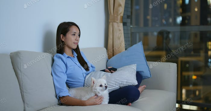 Woman watch tv with her dog at night