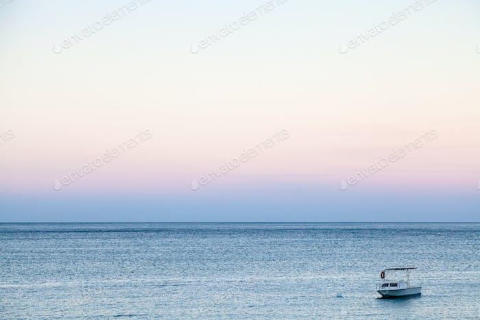 Boot im Meer in blau und rosa Sommerdämmerung