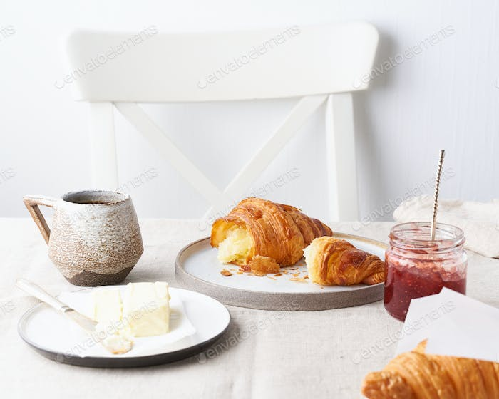 Coffee with a croissant. Sunny morning, breakfast with fresh pastries. Traditional french breakfast