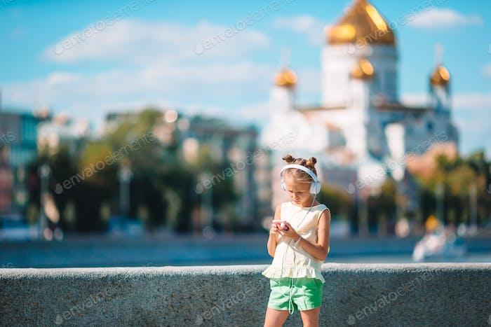 Kleine entzückende Mädchen hören Musik in der park