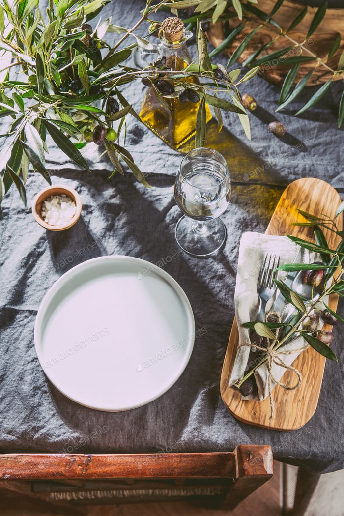 Table setting. Empty whie plate, cutlery and olive tree branches decorations on gray linen