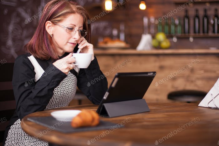 Businesswoman looking at tablet while talking having a conversation on her phone