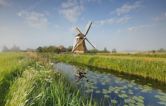 encantador molino de viento por río sobre el cielo azul