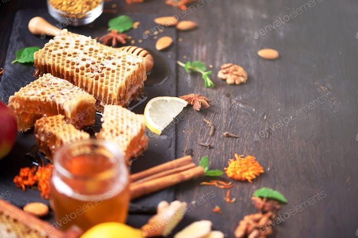 Autumn picnic. Herbal tea, honey and bee products, apple, lemon, calendula, spices on dark
