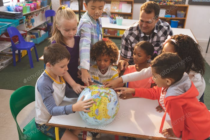 Schoolteacher showing at his school kids the earth globe in classroom at school