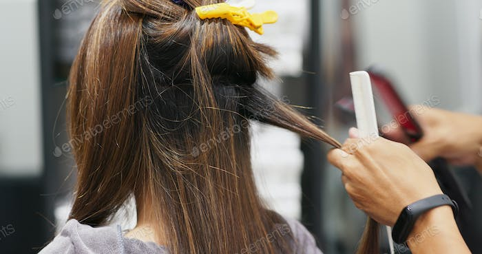 Woman having hair straightening treatment in hair salon