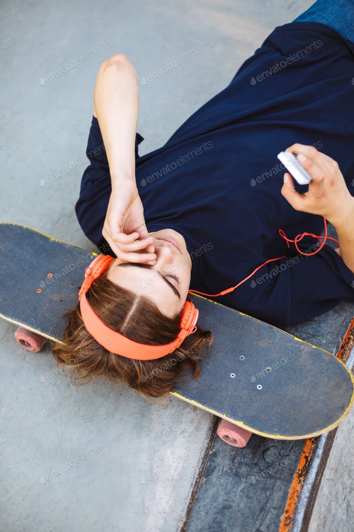 Portrait of young guy in orange headphones lying on skateboard w