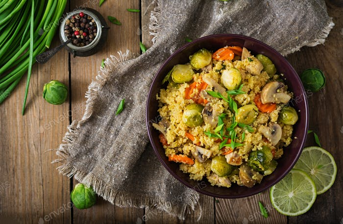 Vegetarian couscous salad with brussels sprouts, mushrooms, carrots and spices. Fitness food.