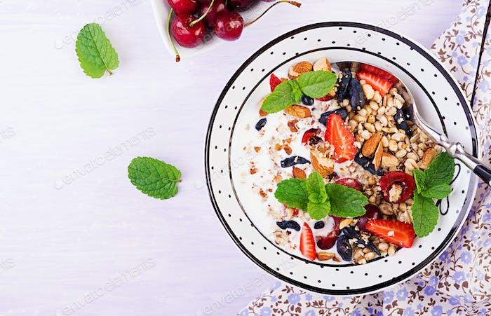 Gesundes Frühstück - Müsli, Erdbeeren, Kirsche, Geißblatt Beeren, Nüsse und Joghurt