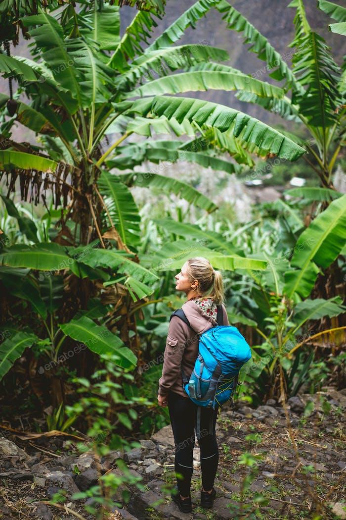 Mujeres jóvenes rubias con mochila azul admiran la plantación de plátanos en la ruta de trekking a paul valley