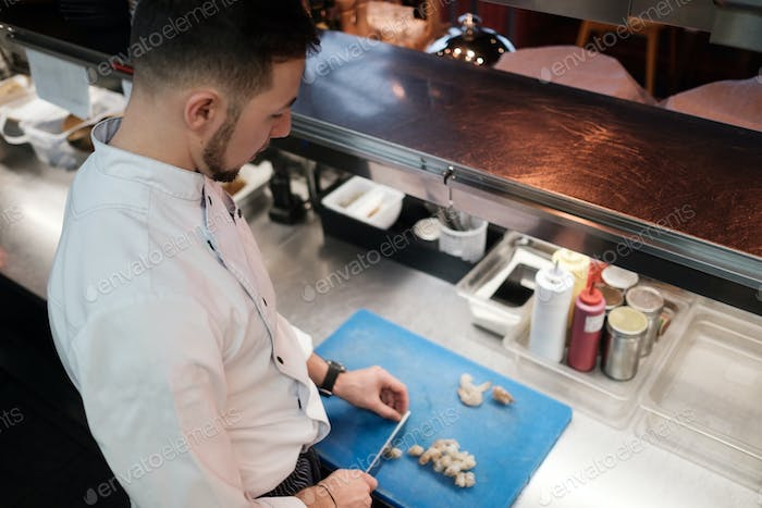 Chef is cutting raw shrimp with big special knife