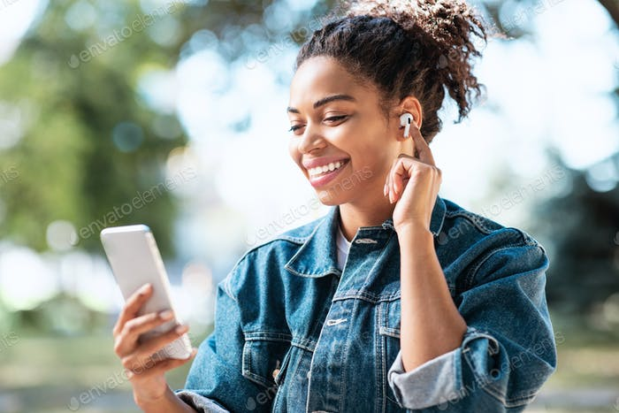 African Woman Using Cellphone And Earbuds Making Video Call Outdoors