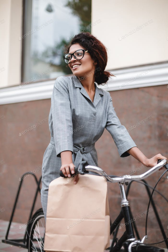 Portrait of young lady with dark curly hair in gray dress riding bicycle with paper bag in hand