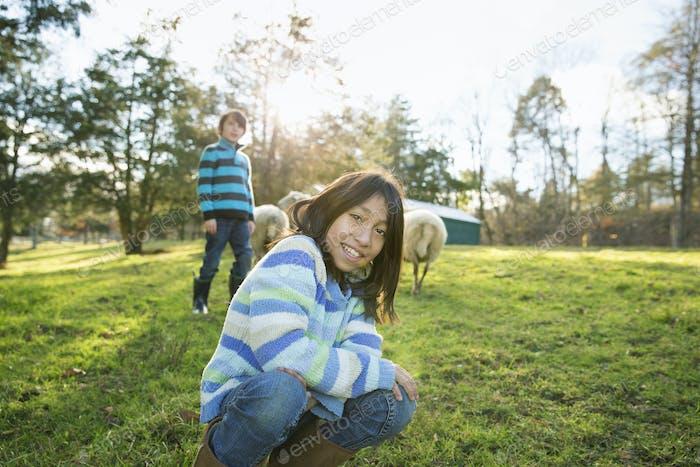 Zwei Kinder in einem Tierschutzgebiet, in einem Tiergehege mit einer Gruppe von Schafen.