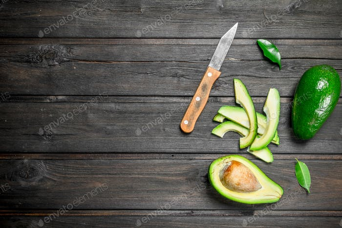 Avocado and small slices of avocado with a knife.