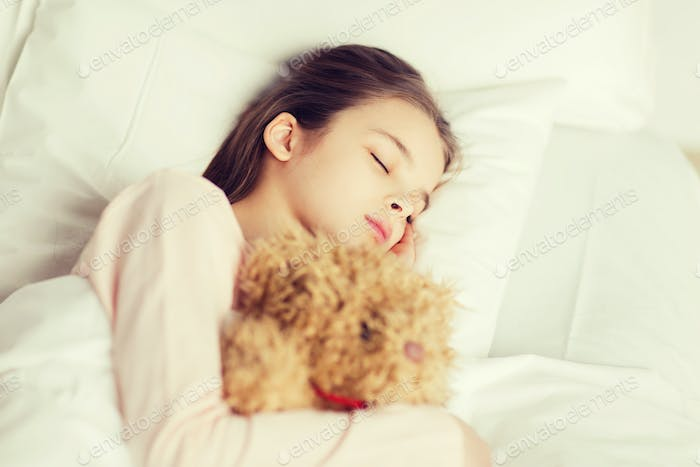 girl sleeping with teddy bear toy in bed at home