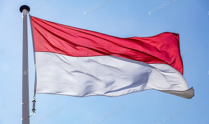 Indonesian flag waving against clear blue sky