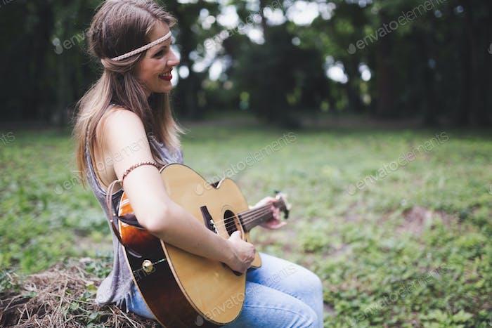 Beautiful woman playing guitar in nature