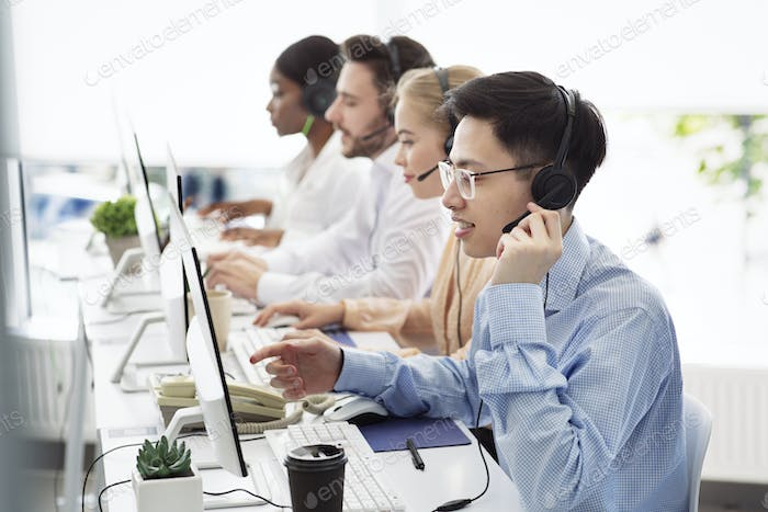 Telecommunications concept. Positive hotline consultants selling goods or services at call centre