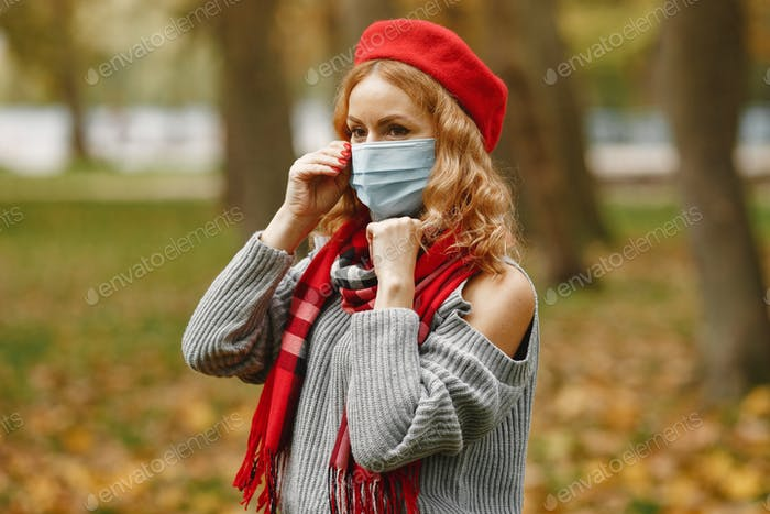 Woman in a mask stands in a park