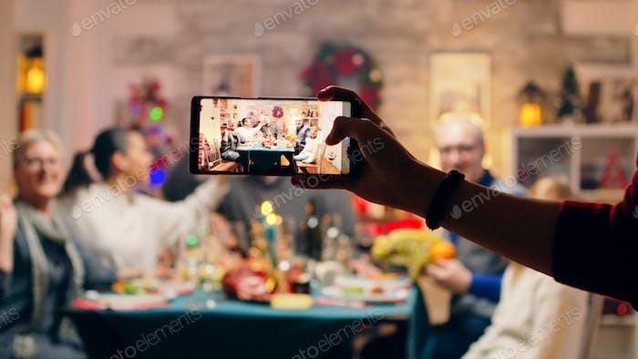 Menina tomando um retrato de família com seus telefones