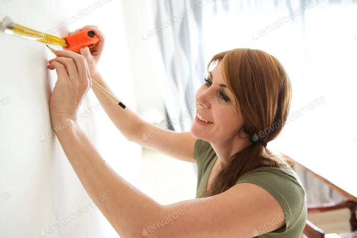 Happy mature woman marking wall