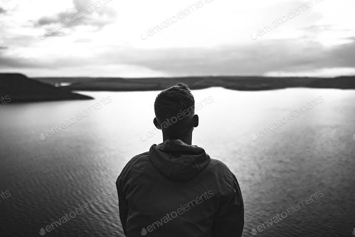 Hipster traveler in windbreaker standing alone on top of rock mountain
